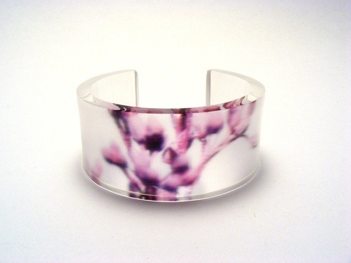 Hand made acrylic bangle featuring image of purple blossom against a transparent background.