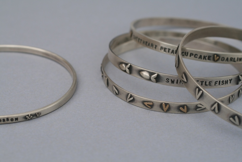 Selection of narrative bangles - silver, 9ct yellow gold and oxidised silver