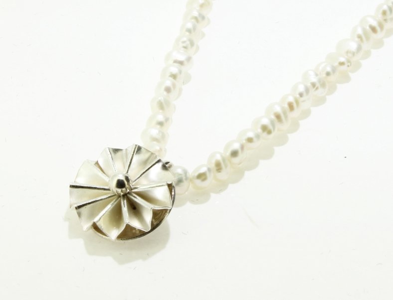 Silver and gold rosette on fresh water pearls