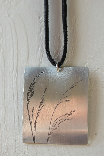 Silver pendant on thong