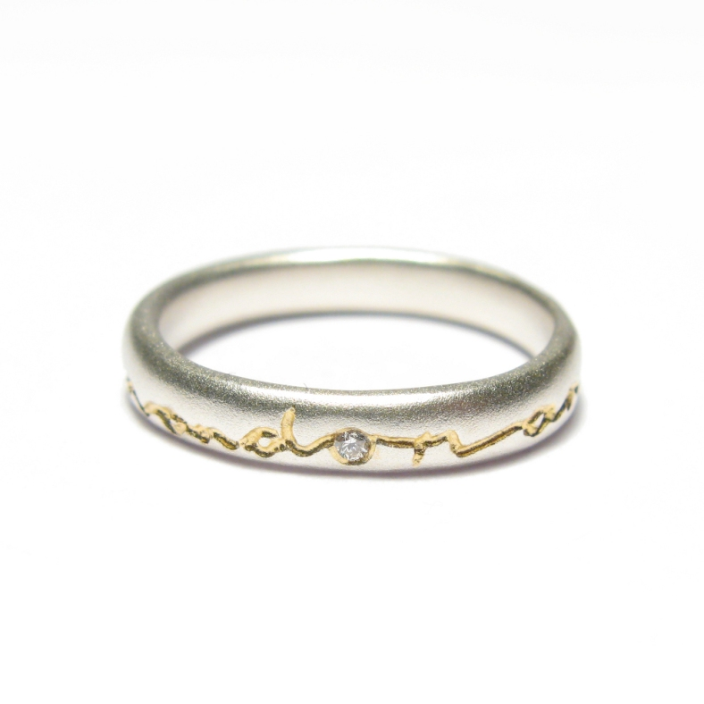 And on - silver ring etched with 22ct gold and includes a diamond in the 'o'