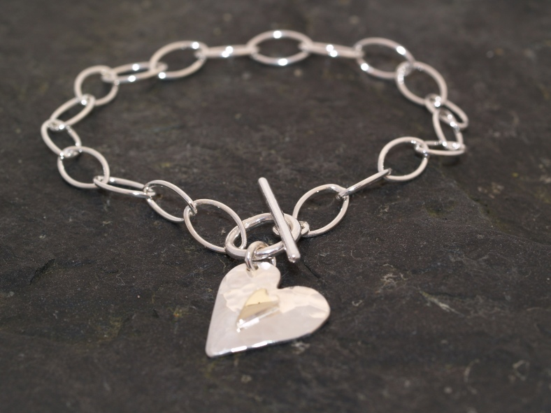 Silver and 9ct gold heart charm bracelet
