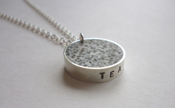 Necklace using tea leaves set in white resin encased with silver