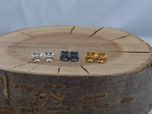 Silver blossom studs sitting with oxidised silver and gold plate blossom studs
